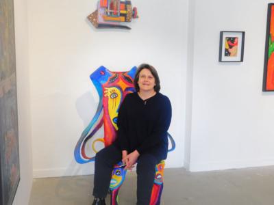 Françoise Monnin assise sur une œuvre de l'artiste Badia © photo Audrey Durand
